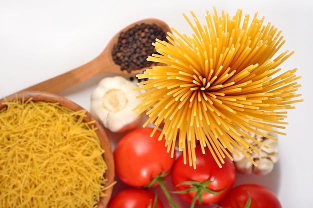 Pasta italiana cruda, ramo di pomodori maturi e pepe nero su
