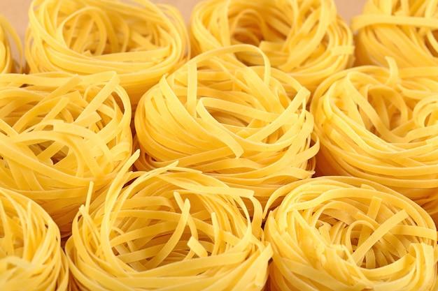 I nidi di tagliatelle di pasta italiana cruda si chiudono in su