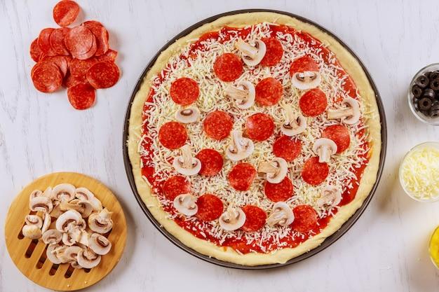 Pizza cruda con peperoni e funghi.