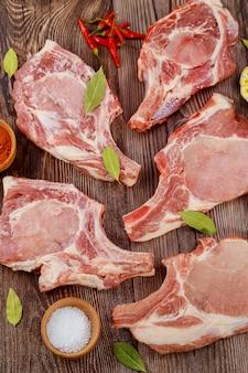 Costolette di maiale crude costola con spezie su sfondo di legno.