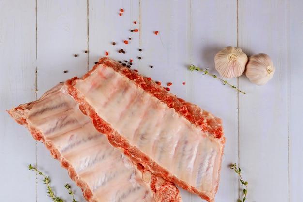 Costole di carne di maiale crude con aglio e le erbe su superficie bianca
