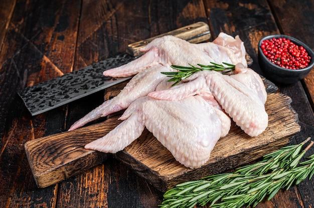 Ali di pollo crude crude carne di pollame su un tagliere di macelleria con mannaia di carne. sfondo in legno scuro. vista dall'alto.
