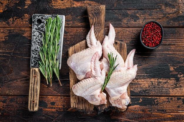 Ali di pollo crude crude carne di pollame su un tagliere di macelleria con mannaia di carne.