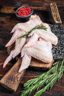 Alette di pollo crude crude carne di pollame su un tagliere da macelleria con mannaia