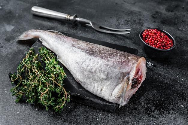 Pesce intero di merluzzo crudo crudo su tavola di marmo con timo. vista dall'alto.