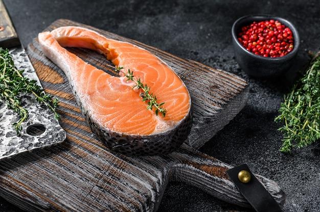 Salmone crudo affettato a forma di bistecca con pepe. vista dall'alto.