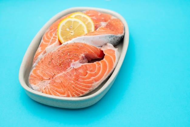 Salmone crudo con limone sul piatto su sfondo blu