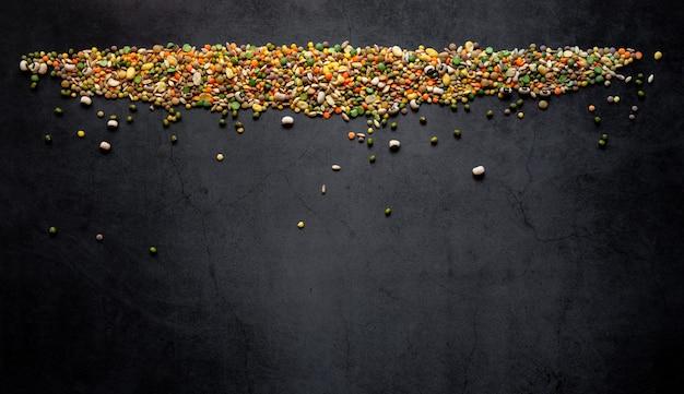 Zuppa cruda di vari legumi misti colorati con orzo, farro, piselli, fagioli, lenticchie e fave su sfondo scuro