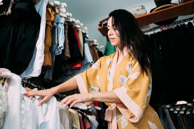 Donna indecisa in cerca di vestiti nel guardaroba