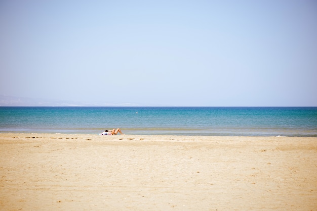 Signora indefinita sdraiata sulla spiaggia estiva