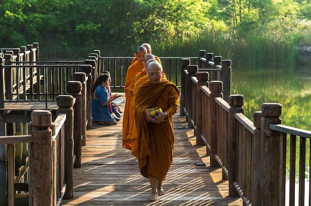 Le persone non definite stanno preparando cibo per l'elemosina al buddista