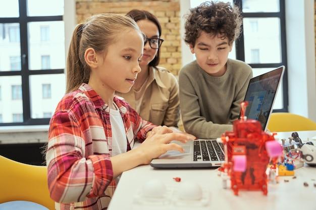 Comprendi come funziona la tecnologia, la bambina carina impara a programmare usando il laptop durante la lezione di staminali