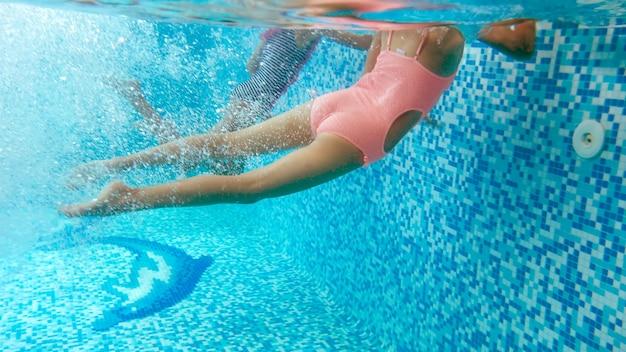 Immagine subacquea di due ragazze adolescenti che si tuffano e nuotano sott'acqua in piscina