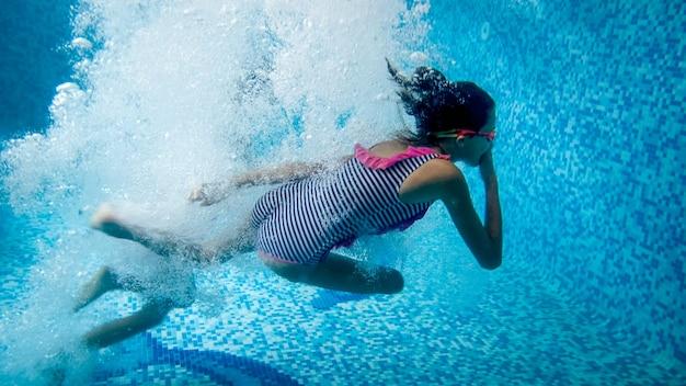 Immagine subacquea di due ragazze adolescenti che saltano in piscina al resort estivo dell'hotel