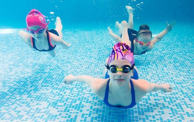 Foto subacquea di giovani amici in piscina.