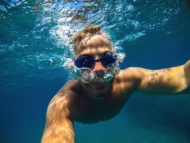 Vista subacquea di un giovane uomo subacqueo che nuota nel mare turchese per le vacanze estive mentre si prende un selfie.