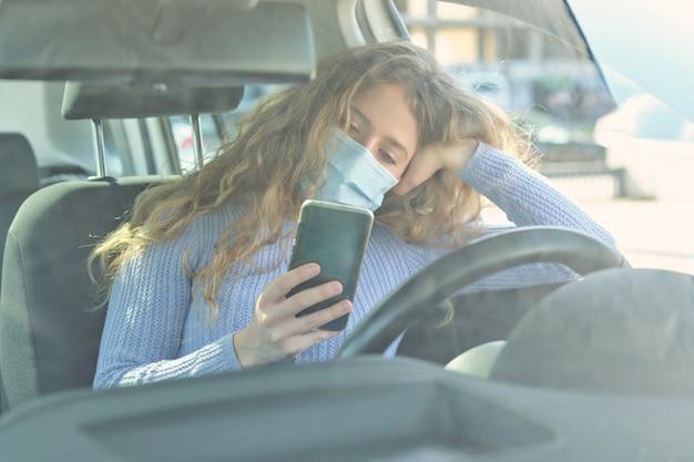Autista femminile impassibile che utilizza lo smartphone in auto
