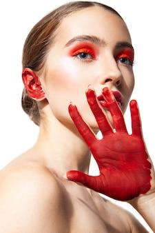 Modello femminile impassibile con labbra rosse e ombretti in piedi con la mano dipinta su sfondo bianco in studio e distogliere lo sguardo