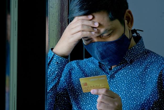 Un uomo asiatico disoccupato guarda con ansia la sua carta di credito durante il blocco covid-19