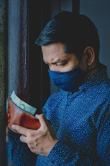 Un uomo asiatico disoccupato guarda con ansia il suo portafoglio durante il blocco covid-19