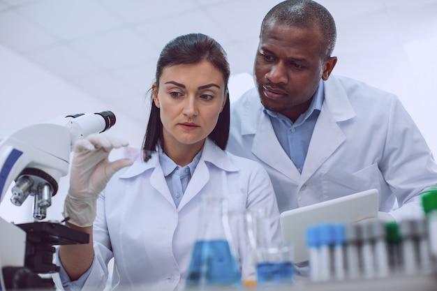 Risultati imprevisti. una ricercatrice esperta seria che esamina un campione e il suo collega in piedi dietro di lei
