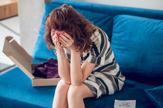 Inaspettato. giovane dai capelli scuri che sembra infelice e frustrato mentre apre la scatola