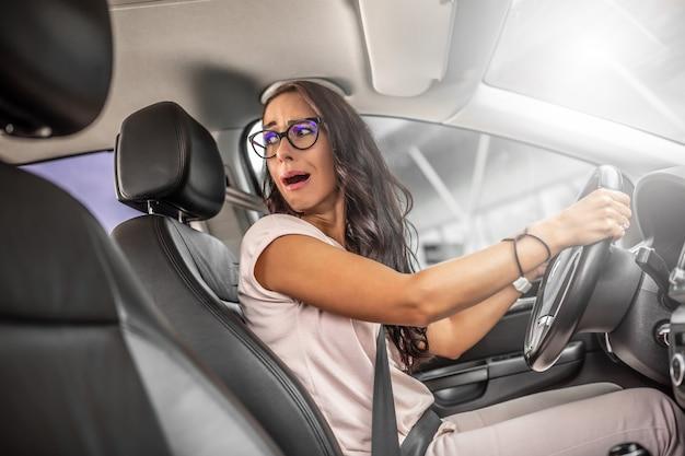 L'autista inesperto con l'espressione facciale spaventata inverte l'auto guardando sopra la sua spalla.