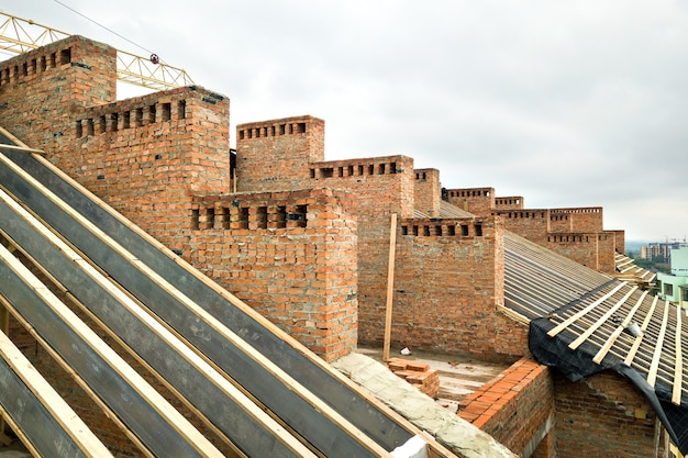 Edificio in mattoni incompiuto con struttura del tetto in legno in costruzione.
