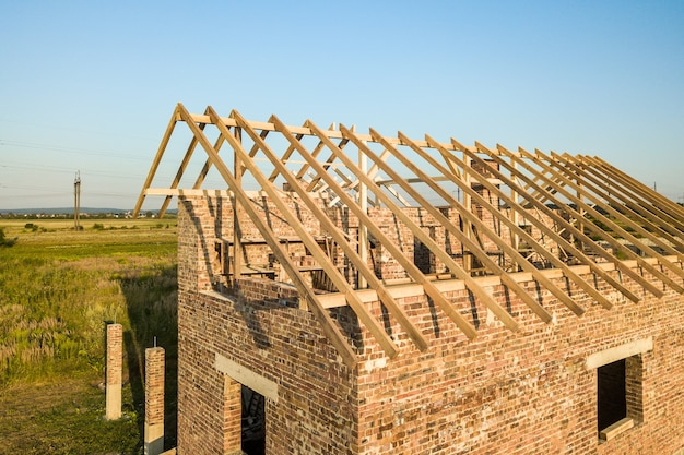 Casa in mattoni non finita con struttura del tetto in legno in costruzione.