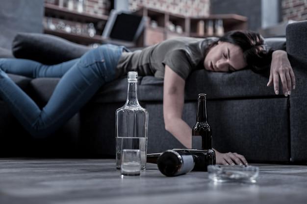 Bevanda incompiuta. messa a fuoco selettiva di mezza bottiglia vuota di vodka in piedi sul pavimento con una giovane donna ubriaca che dorme in background