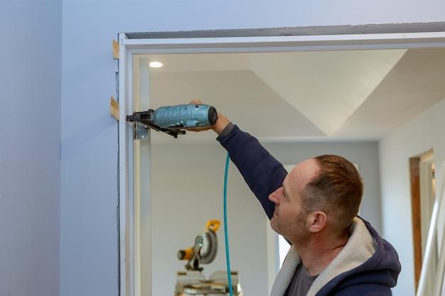Installazione di una casa incompiuta nuove porte interne in legno nell'uso del chiodo della pistola ad aria compressa nell'inchiodamento sui lavori di finitura
