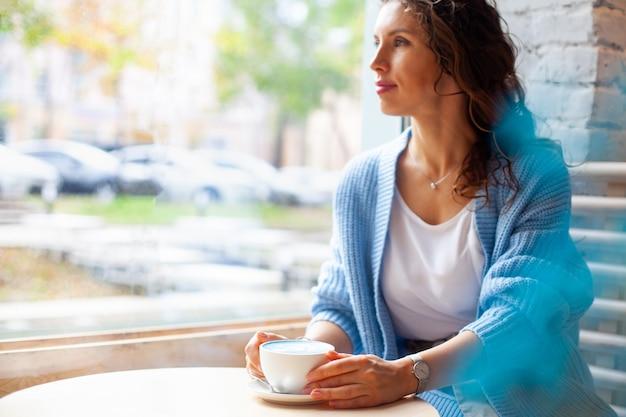 Donna felice sfocata con capelli ondulati lunghi in maglione caldo che tiene tazza di latte blu caldo. bevanda e colore alla moda. il latte del tè blu è fatto con fiori di pisello farfalla. bevanda salutare a base di erbe