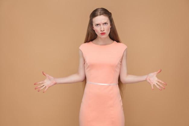 Donna infelice di rabbia con le mani in su che guarda l'obbiettivo. emotiva carina, bella donna con trucco e capelli lunghi in abito rosa. indoor, girato in studio, isolato su sfondo marrone chiaro o beige.
