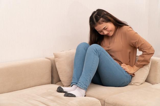 Donna asiatica infelice che si siede sul sofà e che tiene sullo stomaco che soffre dal dolore mestruale