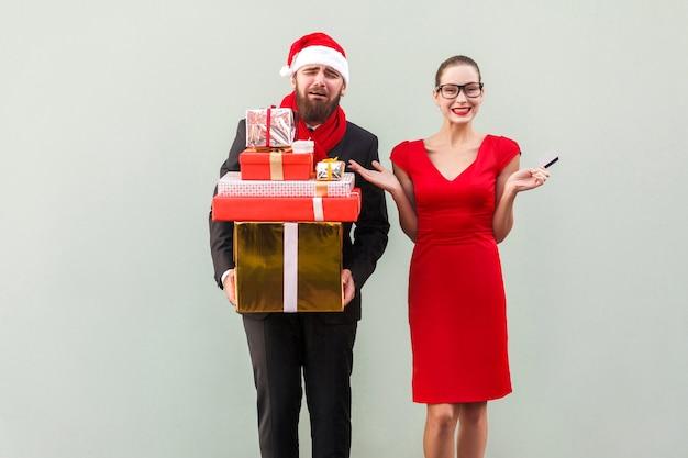Infelice uomo barbuto ben vestito che tiene in mano molte scatole regalo e piange, donne con occhiali neri e vestito rosso che guarda l'obbiettivo, sorridente a trentadue denti e mani sui lati. foto in studio