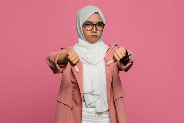 Bella donna asiatica infelice che mostra pollice verso il basso