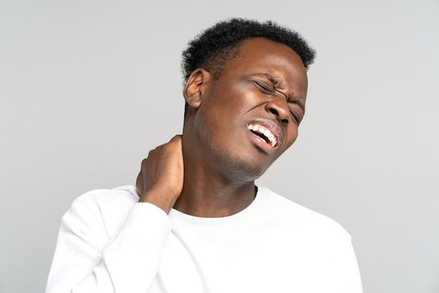 Uomo di colore infelice che soffre di dolore al collo nervo pizzicato nella schiena ha problemi alla colonna vertebrale