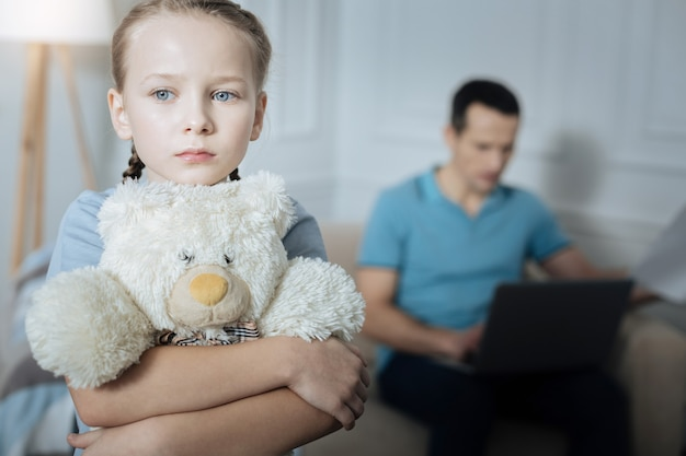 Bambina dai capelli biondi infelice dagli occhi azzurri che tiene il suo giocattolo e in piedi nella stanza mentre il suo papà lavora in background