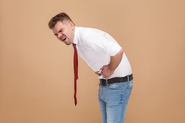L'uomo d'affari infelice ha mal di stomaco. concetto di uomini d'affari, emozioni e sentimenti buoni e cattivi. studio girato, isolato su sfondo marrone chiaro