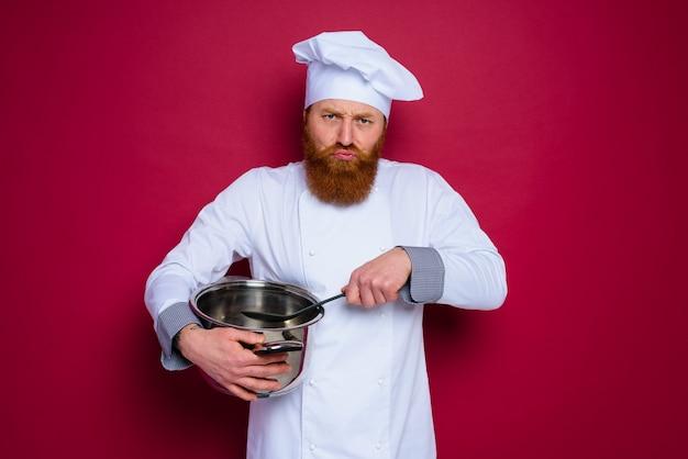 Lo chef infelice con barba e grembiule rosso è pronto per cucinare
