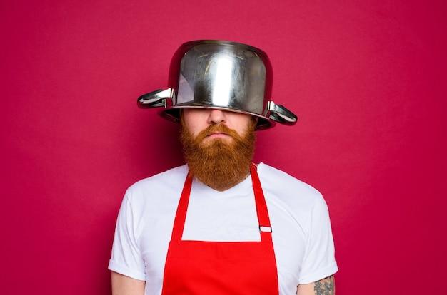 Lo chef infelice con barba e grembiule rosso gioca con la pentola