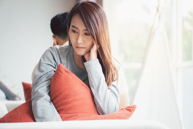 Coppia infelice seduta una dietro l'altra sul divano ed evitare di parlare o guardarsi