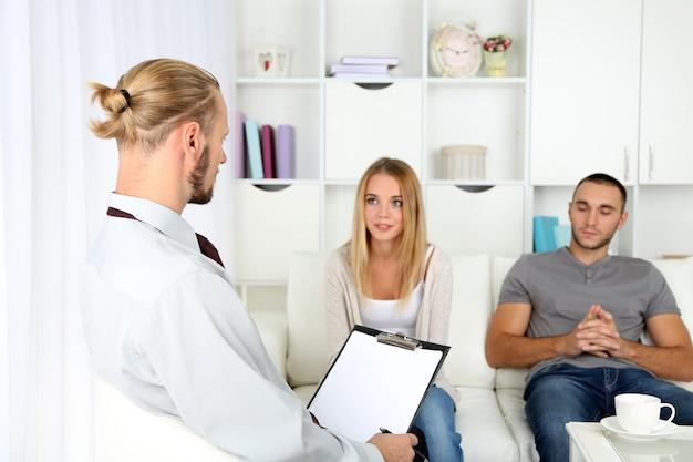 Coppia infelice che non parla sul divano durante la sessione di terapia