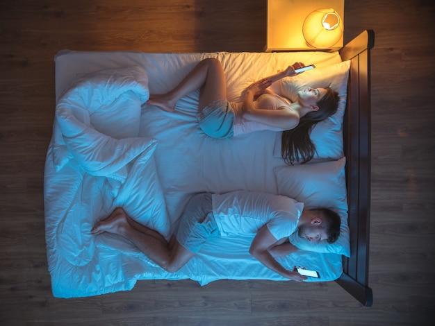 La coppia infelice con lo smartphone giaceva sul letto. notte. vista dall'alto