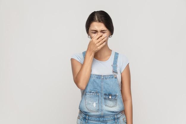 Giovane zingara adulta infelice e depressa, che si vergogna o si ammala, copre il viso con entrambe le mani, tiene gli occhi chiusi. studio isolato girato su sfondo grigio.