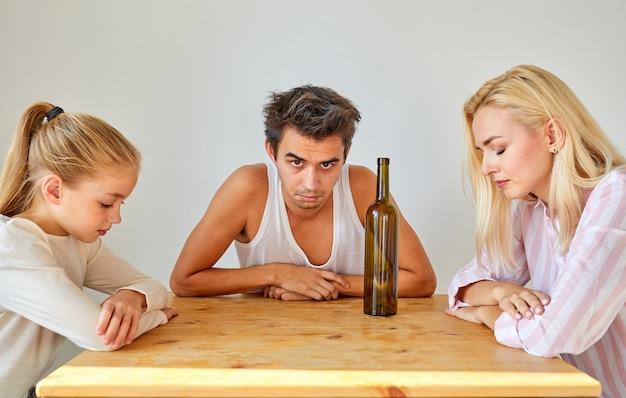 Famiglia infelice seduta a tavola insieme, l'uomo ubriaco porta solo guai alla famiglia