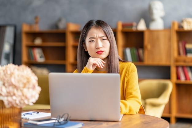 Donna asiatica accigliata infelice che dimentica smth che lavora al computer portatile