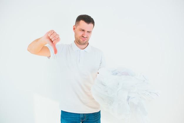 Ragazzo infelice guarda i sacchetti di plastica in mano e mostra il pollice verso il basso. male per l'ambiente.