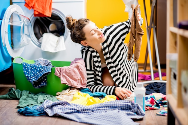Casalinga infelice che tiene i calzini vicino alla lavatrice con vestiti colorati a casa