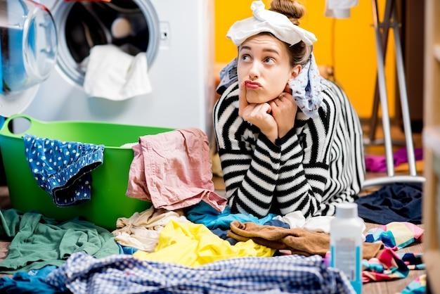 Casalinga infelice seduta con i calzini vicino alla lavatrice con vestiti colorati sul pavimento di casa